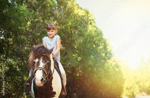 Photo  Cute little girl riding pony in park on sunny day