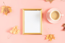 Autumn Creative Composition. Gold Photo Frame, Dry Yellow Leaves, Cup Of Coffee On Pastel Pink Background. Fall Concept. Autumn Background. Flat Lay, Top View, Copy Space