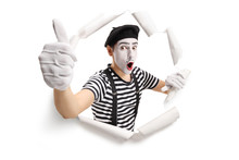 Excited Mime Looking Through A Cracked Paper Hole And Showing Thumbs Up