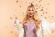 canvas print picture - excited blonde woman in violet satin dress and faux fur coat standing under silver falling confetti on beige background