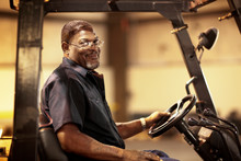Smiling Mature Worker Sitting In Forklift