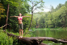 Woman Standing On Log By River
