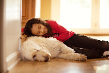 Girl (6-7) Resting With Dog On Floor