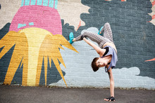 New York State,Woman Doing Handstand In Front Of Graffiti Wall