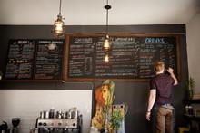 Rear View Of Waiter Writing Menu On Blackboard In Cafe