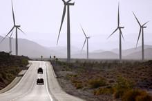 Cars Driving Along Road Near Windmill