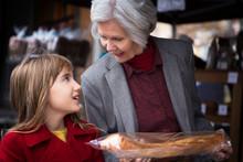 Grandmother With Granddaughter (8-9) Choosing Baguette In Bakery