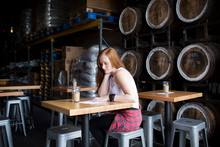 Young Woman Sitting In Brewery