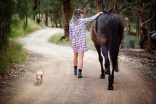 Young Woman Walking With Dog And Horse Outdoors