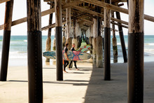 Two Men Walking With Surfboards Under Pier