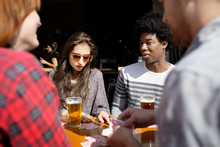 Friends Playing Cards Outside Brewery