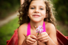 Girl (8-9) With Curly Hair Holding Pink Flower