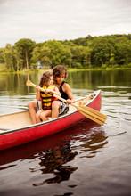 Siblings Rowing Boat In Lake