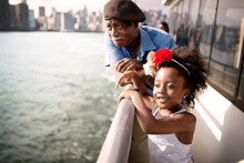 Grandfather And Granddaughter Leaning On Railing On Ship