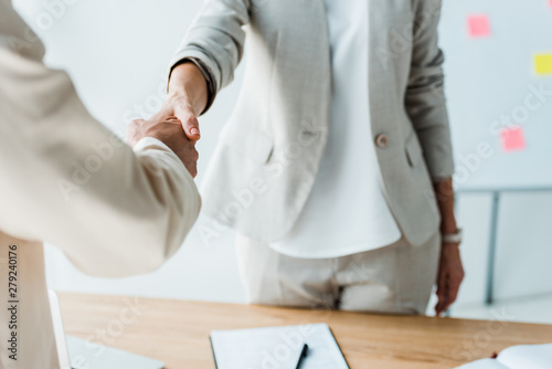 Fotografía  cropped view of recruiter and employee shaking hands while standing in office