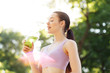 Young beautiful girl drinking green beverage with lime and kiwi from plastic cup take-out food. Smiling slim brunette woman with lemonade in park. Summer cold drinks.