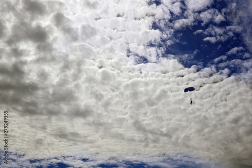 Fotografie, Obraz  silhouette of tandem parachute against the of opposite the wonderful clouds