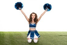 Sexy Happy Cheerleader Girl In Blue Uniform Sitting With Pompoms In Hands On Green Field Isolated On White