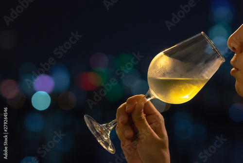 Fotografía  A person sniffing white wine in a glass for wine tasting with colorful city bokeh lights background