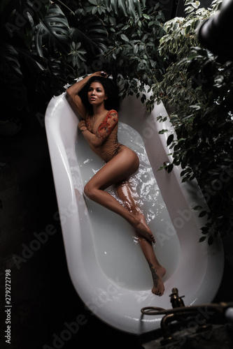 Valokuva A sensual and tempting african american beautiful female model with slim gorgeous body is lying and posing in the bath full of water in the jungles