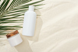 white sunscreen lotion and cream near green palm leaf on sand