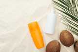 top view of palm leaf, coconuts and sunscreen products on sand