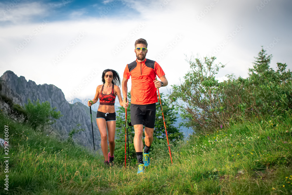 Fototapeta Sporty couple in the mountains with nordic walking poles