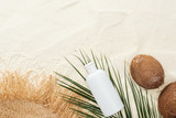 top view of palm leaf, coconuts and sunscreen lotion with straw hat on sand