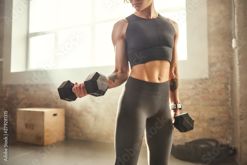 Fototapeta Perfect biceps. Young athletic woman with tattoo on her hand in sportswear exercising with dumbbells while standing in front of window at gym. obraz
