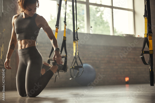 Fototapeta Young athletic woman in sports clothing adjusting trx fitness straps while training in the gym