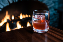 Old Fashioned Cocktail In Front Of A Fire Place