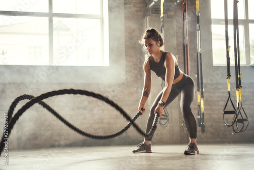 Poster Fitness Preparing for the competition. Young athletic woman with perfect body doing crossfit exercises with a rope in the gym.