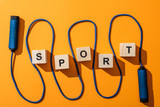 top view of jumping rope near wooden cubes with sport lettering on yellow