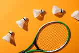 top view of shuttlecocks near badminton racket on yellow