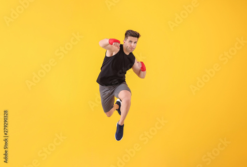 Sporty male kickboxer on color background - 279290328