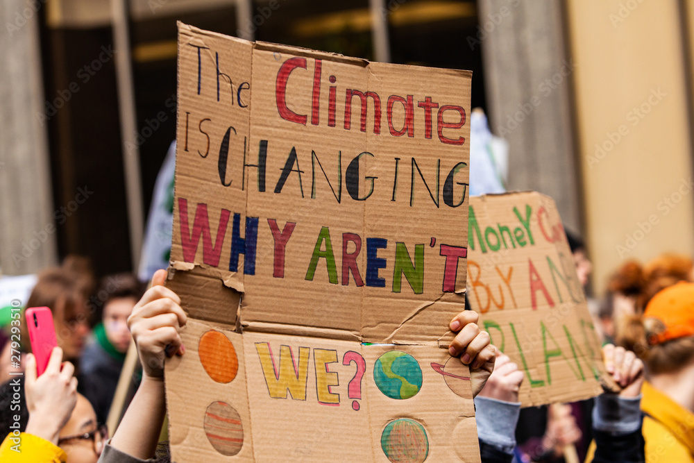Fototapeta Homemade sign at environmental rally. A colorful cardboard placard is viewed close up, saying the climate is changing, why aren't we, in the hands of ecological activists as they protest in the city
