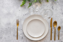 Elegant Table Setting,  White Plate With  Gold Cutlery And  Wine Glasses On Cement Background. Scandinavian Style