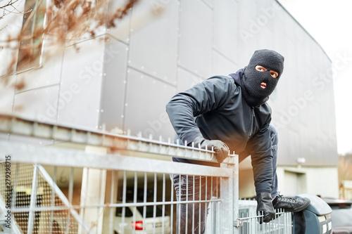 Einbrecher steigt über Zaun von Industrie Firma Fototapeta