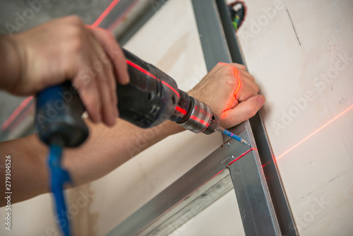 Fotografia, Obraz  Male worker works with profile for drywall, setting, assembling with drill