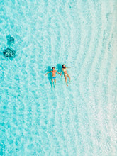 Pregnant Woman With Husband Swim In Blue Sea. Aerial View