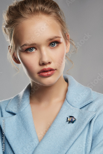 Portrait of girl with tied back fair hair, wearing sky blue coat with bright brooch in view of stripy fish on the lapel Fototapet