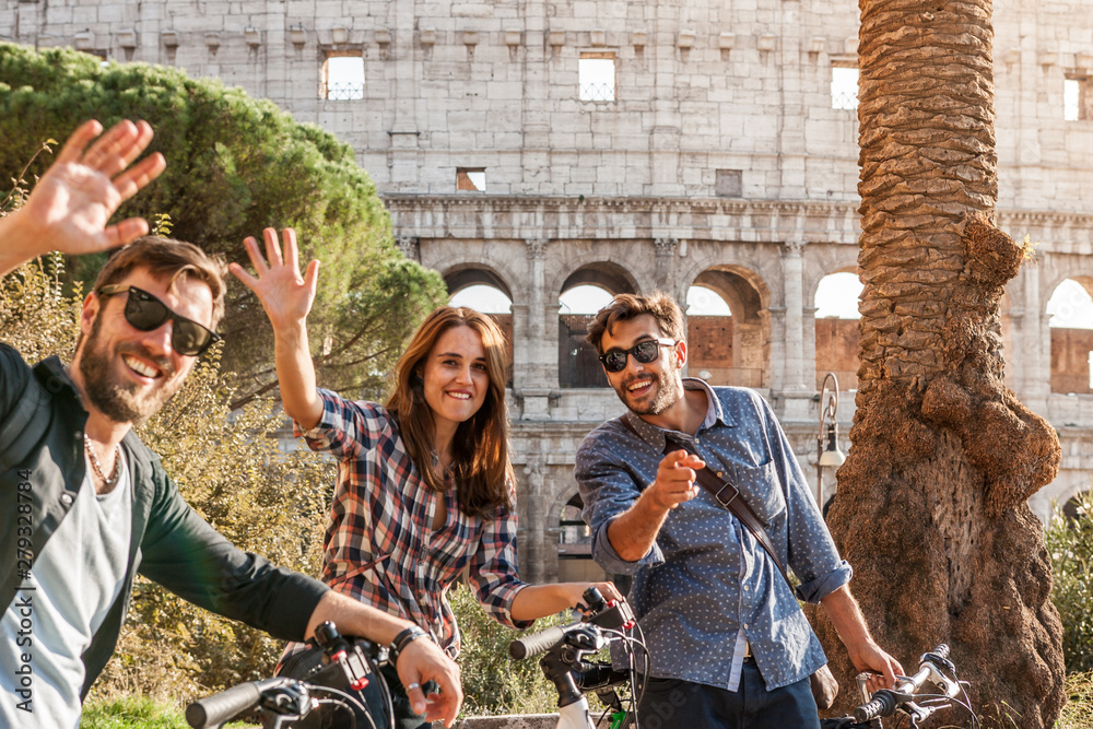 Fototapety, obrazy: Three happy young friends tourists with bikes at Colosseum in Rome having fun posing and waving at camera