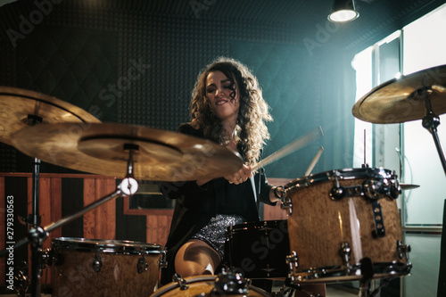 Tela Woman playing drums during music band rehearsal