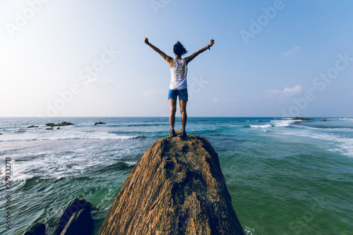 Fotografía  Strong young woman outstretched arms on seaside rock cliff edge