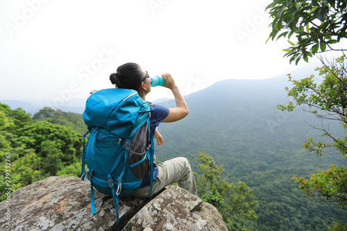 Fotomural  Successful woman hiker enjoy the view and drinking water at mountain peak cliff