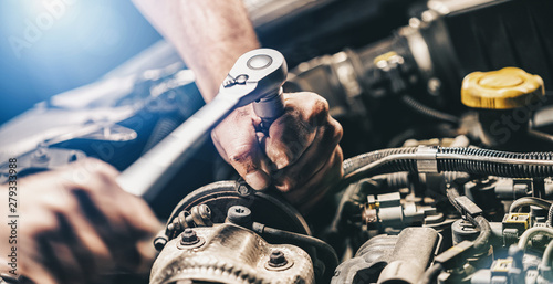Fototapeta Auto mechanic working on car engine in mechanics garage. Repair service concept image. authentic close-up shot obraz
