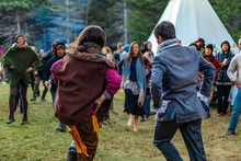 Fusion Of Cultural & Modern Music Event. A Group Of People Are Viewed Dancing Near Tipi Tents In The Woods, Celebrating Native American Culture During A Gathering In Nature.