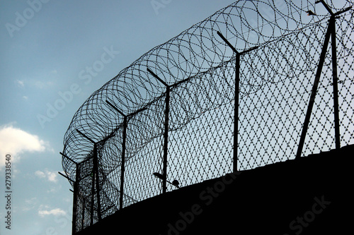 Photo Silhouette of concertina barbed wire on a prison fence