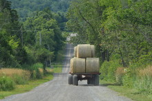 Tractor Pulls Wagon Of Round Bales Of Hay