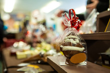 Seasonal Products Sold At Xmas Market. A Gift Wrapped Chocolate Santa Claus With Red Bow Is Seen Up Close On A Shelf At A Christmas Exposition, With A Blank Label And Copy Space To The Left.